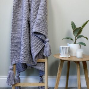 A modern crochet blanket used as home decor hung over a ladder
